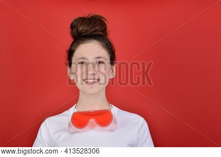Studio Portrait On A Red Background, With A Pretty, Smiling Girl In A White T-shirt, Funny Hair On H