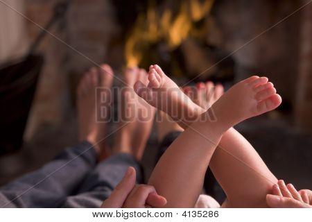 Familias de pies calentamiento en una chimenea