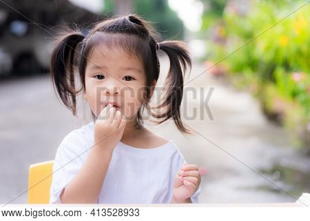 Cute Girl Was Forced By Her Parents To Eat Fresh Fruit. Adorable Kid Tied Up Pigtails Hair, Trying T