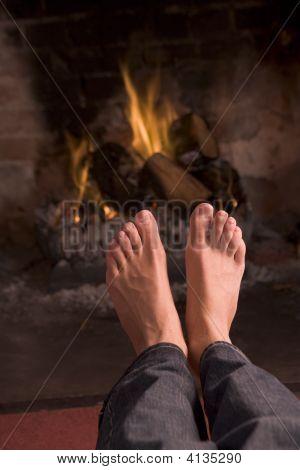 Pies calentamiento en una chimenea