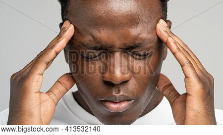 Stressed Black Man Massaging Temples Having Terrible Strong Headache, Eye Closed. Exhausted Upset Af