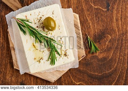 Cheese Feta With Rosemary, Herbs, Olives And Olive Oil On Wooden Cutting Board On Old Wooden Backgro