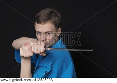 Sports And Martial Arts. Portrait Of A Young Man In A Blue Sportswear With A Sword In His Hands. Hor
