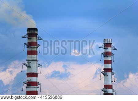 Smoking Chimneys On The Winter Sky Background. Heating Season. The View Of Chimney's Tops Of The The