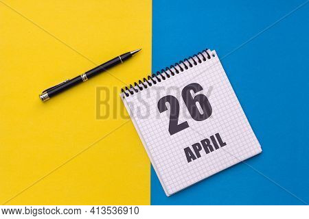 April 26th. Day Of 26 Month, Calendar Date. A Notebook With A Spiral And A Pen Lies On A Yellow-blue