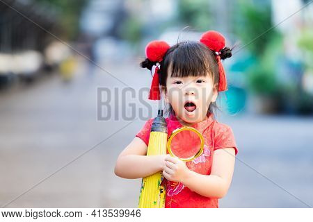 Cute Asian Kid Wearing Red Cheongsam. Child Holds Golden Magnifying Glass And Yellow Vintage Umbrell
