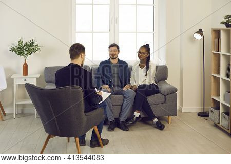Pleased Mixed Race Couple Meeting Family Psychiatrist Or Financial Advisor