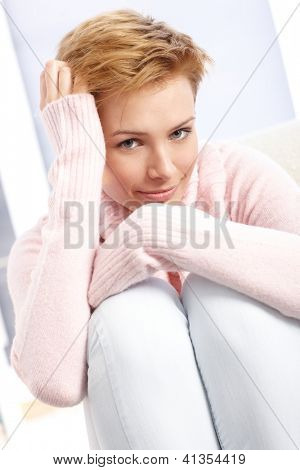 Smiling attractive woman hugging knees, hand in hair.