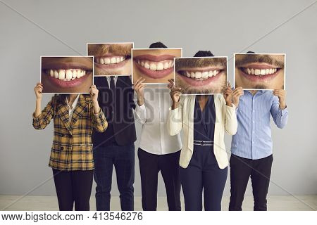 Group Of Diverse People Hiding Behind Big Funny Photos Of Happy Attractive Smiles