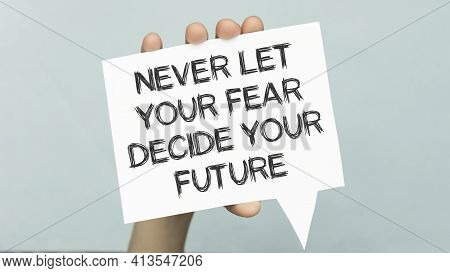 Never Let Your Fear Decide Your Future, Text Words Typography Written On Paper In Hand.