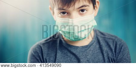 Boy In Medical Face Protection Mask Indoors On Blue Background. Sick Child