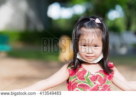 Cute Girl Playing In Hot Sun. Child Sweats On Forehead. Children Puts Mask Under Chin From Discomfor