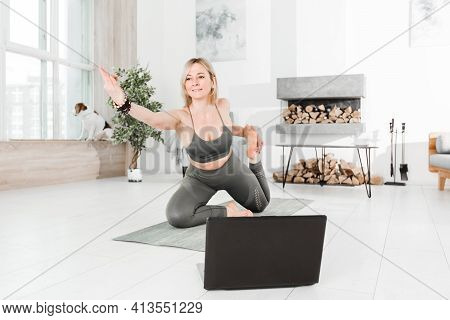 Sports At Home. Online Training. A Woman Is Engaged In Ashtanga Vinyasa Yoga On The Background Of A