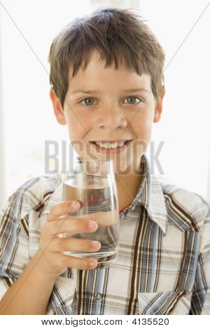 Young Boy Indoors Drinking Water Smiling