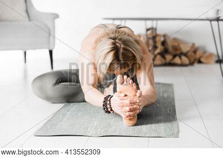 Sports At Home. A Woman Is Engaged In Ashtanga Vinyasa Yoga. Janu Shirshasana Pose