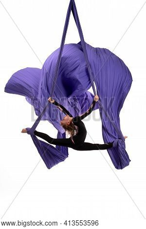 Flexible Woman Doing Aerial Silks Trick On Fabric