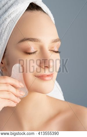 Gua Sha Massage. Facial Lifting. Alternative Selfcare. Relaxed Woman With Nude Makeup Bare Shoulders