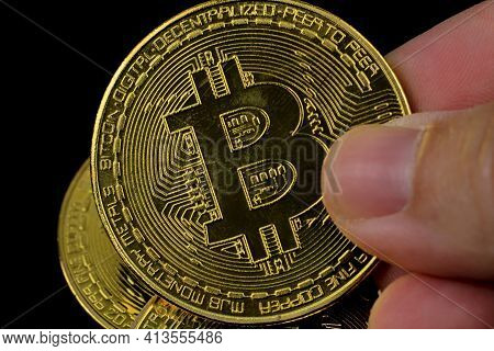 Hand Holding A Bitcoin On Black Background. Many Bitcoins In The Background.