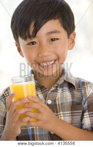 Young Boy Indoors Drinking Orange Juice Smiling
