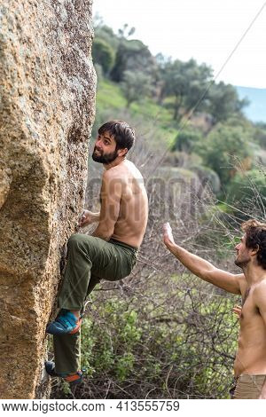 Two Friends Train To Climb A Large Boulder, A Man Is Engaged In Rock Climbing In Nature, A Man Belay