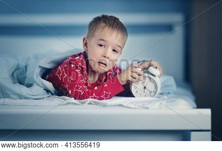 Sleepy Boy Lying In Bed With Blue Beddings. Tired Child In Bedroom Sleeping. Little Kid Lying Asleep