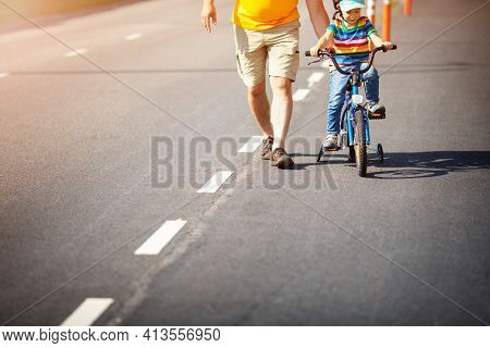 A Child On A Bicycle In Helmet With Father On Asphalt Road. Little Boy Learning To Ride On Bike With