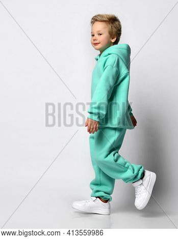 Full Length Portrait Of A Little Stylish Boy In A Warm Sports Suit On A Gray Background. Boy Dressed