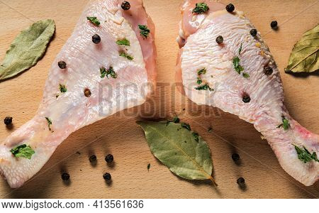 Сhicken Legs On A Cutting Board With Spices Close-up. The Idea Of Cooking Lunch Or Breakfast In A Re