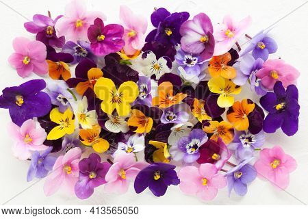 Spring or summer flower composition with edible pansy and violets on white background. Flat lay, copy space. Healthy life concept.