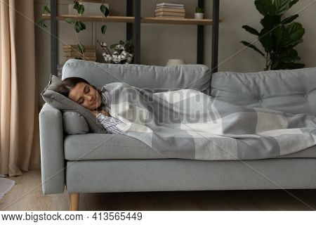 Peaceful Woman Sleeping Under Warm Blanket On Cozy Couch