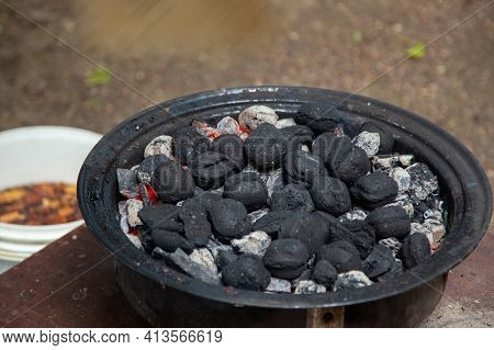 Charcoal Bricks Burning In A Barbecue Smoker At The Cottage.