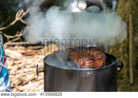 Lifting The Lid To Check On A Large Beef Brisket On A Smoker