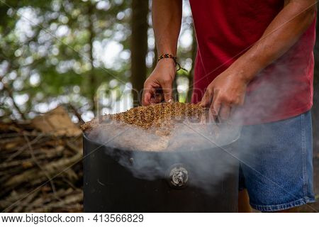 Mans Hands Placing A Large Beef Brisket On A Smoker