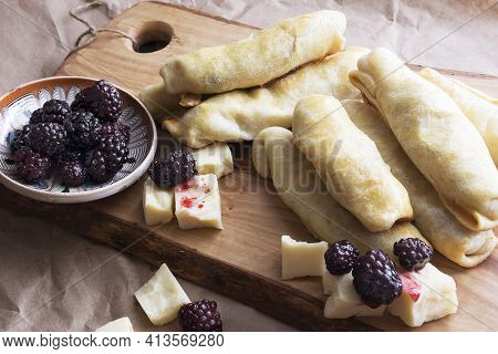 Oven Fresh Home Made Baked Stuffed Rolls, Cheese And Blackberry. Delicious Pastries On Wooden Cuttin