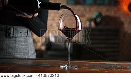 Elegant woman pouring red wine from wine bottle to wine glass at home in a cosy dark room.