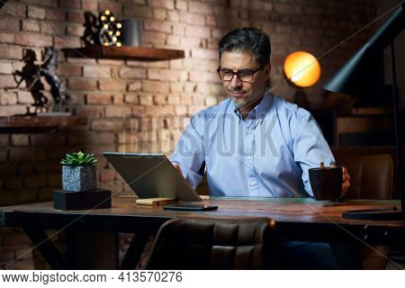 Man working from home in home office with tablet computer at desk in trendy room.