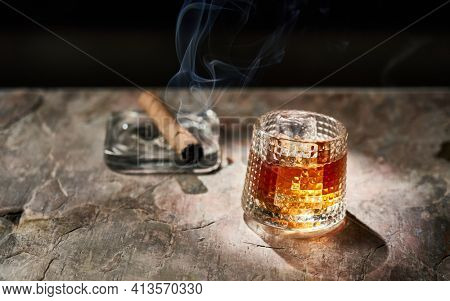 Glass of whiskey and smoking cigar on table. Copy space, black background. Whiskey, brandy, cognac, alcoholic drink .