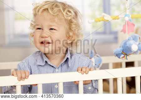 Portrait of cute blonde child playing in crib.