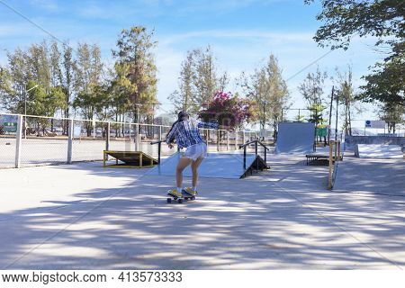 Young Asian Women Play Surf Skate Board At Park Skate Ramp Outdoors On Morning. Happy Women Play Sur