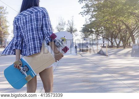 Close Up On Young Women Hand Hold Skateboard, Surf Skate On Public Skate Ramp Park Background. Free