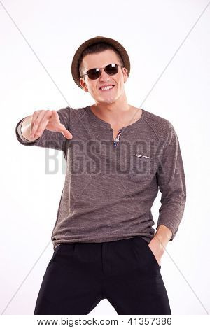 waste-up picture of a casual young man wearing a trilby and sunglasses, pointing towards the camera and holding the other hand in his pocket, with a grin on his face on a light background