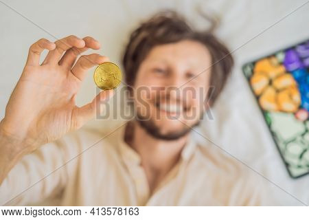 Young Man, A Digital Artist, Creates Digital Art On A Tablet At Home And Shows A Coin With The Inscr
