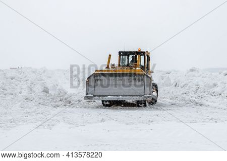 Yellow Bulldozer Removes Snowdrifts In A Severe Snowstorm At Winter