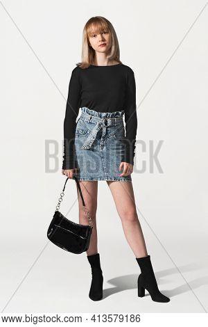 Blonde girl in black sweater and denim skirt for winter apparel shoot