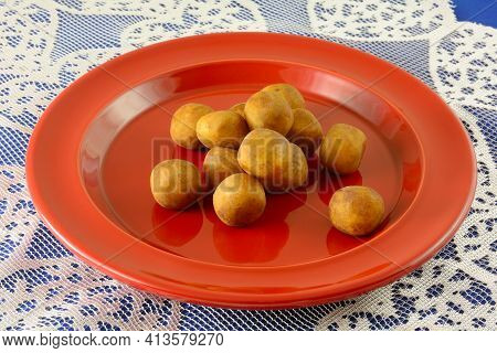 Cocoa Dusted Marzipan Balls On Red Plate On Lace Table Runner On Blue Tablecloth