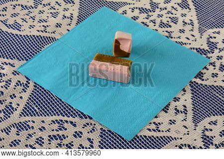Strawberry And Licorice Candy Caramels On Blue Napkin On Lace Tablecloth