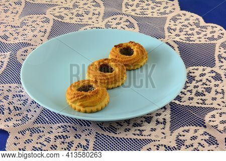 Three Sour Cherry Butter Cookies On Blue Plate On Lace Table Runner On Blue Tablecloth