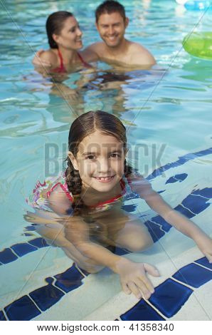 Portrait of a cute preadolescent girl smiling with parents in the background