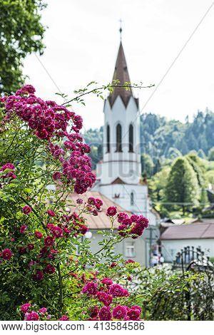 Evangelic Church And Red Roses, Lubietova Village, Slovak Republic. Architectural Theme.