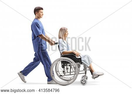 Full length profile shot of a male healthcare worker pushing a female patient in a wheelchair isolated on white background